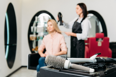 hairdresser drying customer hair with round hair brush on foreground
