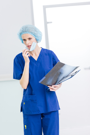 female surgeon in medical cap and mask holding x-ray in clinic
