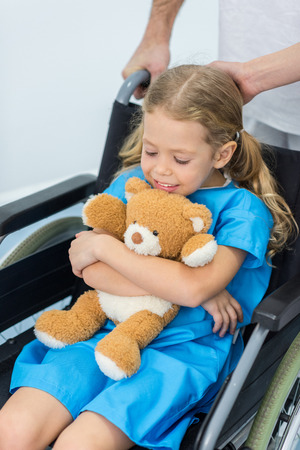 little child with teddy bear sitting in wheelchair in hospital Stock fotó