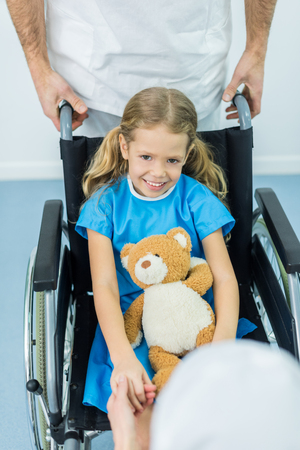 smiling kid sitting with soft toy on wheelchair and looking at camera