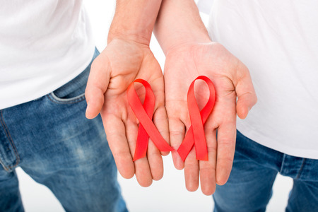 cropped shot of gay couple holding aids ribbons isolated on white