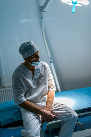 upset doctor sitting on medical bed and looking away Stockfoto