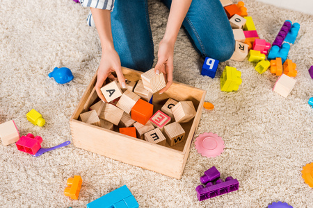 cropped image of woman collecting children toys Reklamní fotografie - 114408871