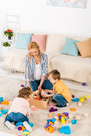 overhead view of pregnant mother collecting toys with children Фото со стока