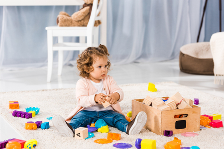 adorable little child sitting on carpet and playing with toys 写真素材