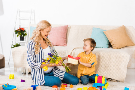 little boy presenting to smiling pregnant mother tulip flowers and heart shaped gift box