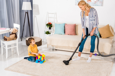 cute little boy playing with colorful blocks and looking at pregnant mother cleaning carpet with vacuum cleaner 스톡 콘텐츠