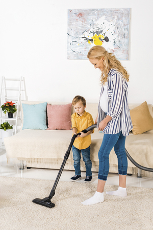 smiling pregnant woman with adorable little son cleaning carpet with vacuum cleaner together
