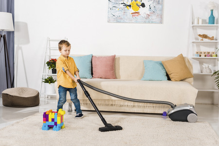 cute little boy cleaning carpet with vacuum cleaner