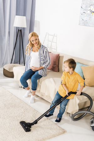 happy pregnant woman sitting on sofa and looking at cute little boy cleaning carpet with vacuum cleaner 스톡 콘텐츠