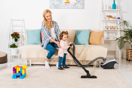 smiling pregnant woman looking at cute little daughter holding vacuum cleaner at home