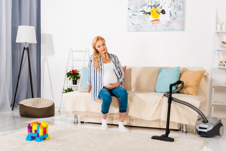blonde pregnant woman sitting on sofa and looking at carpet with colorful blocks and vacuum cleaner 스톡 콘텐츠