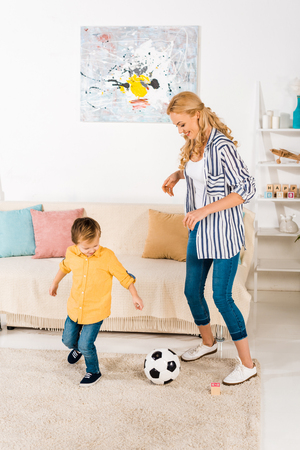 happy mother and little son playing with soccer ball at home