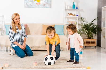 smiling mother looking at cute little children playing with soccer ball at home Stock Photo
