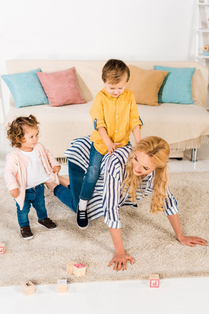 happy mother playing with adorable little kids at home Фото со стока