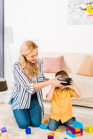 beautiful mother with adorable little son using virtual reality headset at home Stock Photo