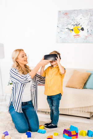 smiling mother with cute little son using virtual reality headset at home