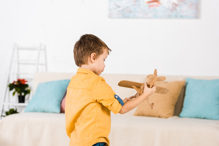 little adorable little boy playing with wooden toy airplane at home