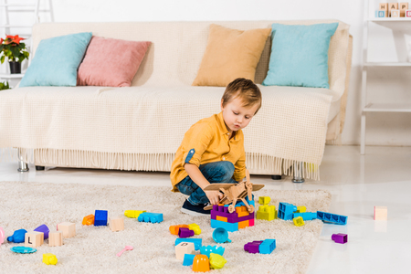 adorable little boy playing with toy airplane and colorful blocks at home