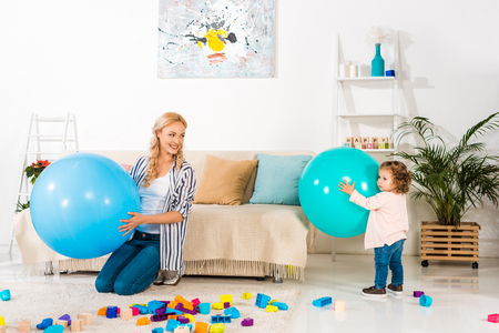 beautiful happy mother and infant daughter playing with fitness balls and colorful blocks at home Stock Photo