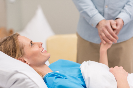 cropped image of husband holding hands with sick wife Stock Photo
