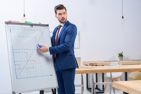 businessman presenting diagram chart at meeting and looking away