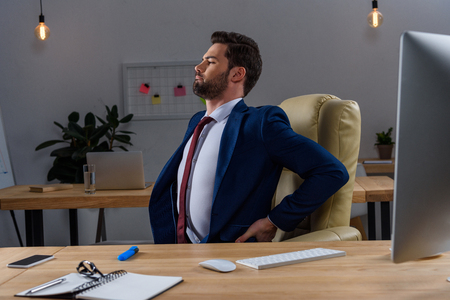 young businessman sitting in chair and having pain in back