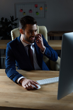 smiling businessman talking by smartphone and using computer Stock Photo