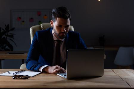 handsome businessman working at laptop in dark office Stock Photo