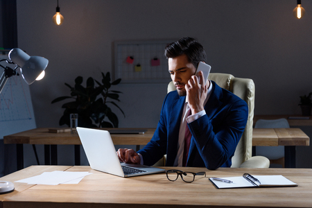 businessman talking by smartphone and working with laptop