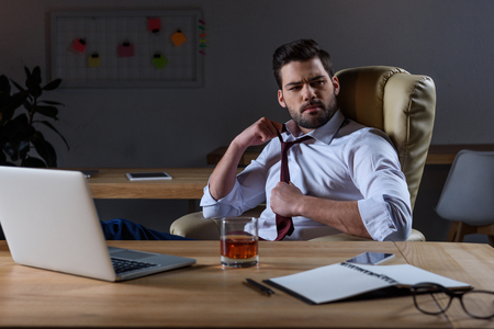 tired businessman loosen tie and sitting at table with glass of whiskey