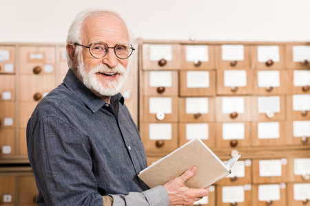 smiling senior male archivist holding book and looking at camera Foto de archivo - 114410052