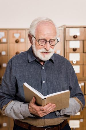 senior male archivist reading book Foto de archivo - 114410053
