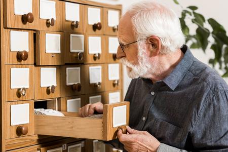 senior male archivist searching for catalogs Foto de archivo - 114410058