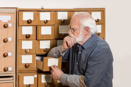 thoughtful senior male archivist leaning on catalog boxes