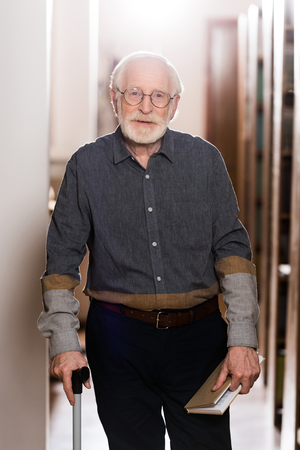 grey hair librarian with walking stick and book looking at camera