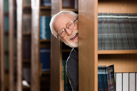 happy grey hair librarian looking out from shelf Foto de archivo - 114410069