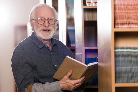 smiling grey hair librarian holding book and looking at camera Foto de archivo - 114410073