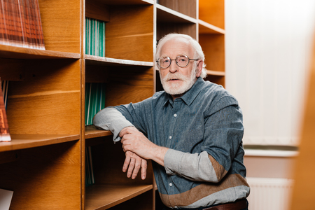 grey hair librarian leaning on shelves and looking at camera