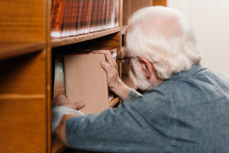 grey hair librarian searching for book on shelves Reklamní fotografie
