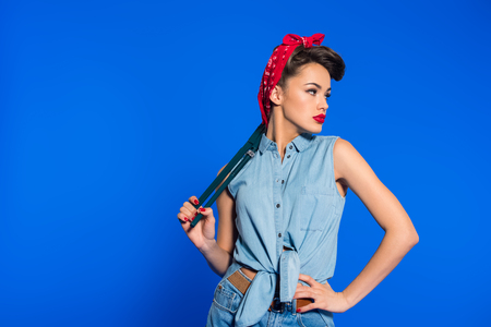 fashionable young woman in pin up style clothing with wrench isolated on blue