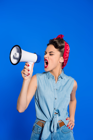 fashionable young woman in pin up style clothing with loudspeaker isolated on blue