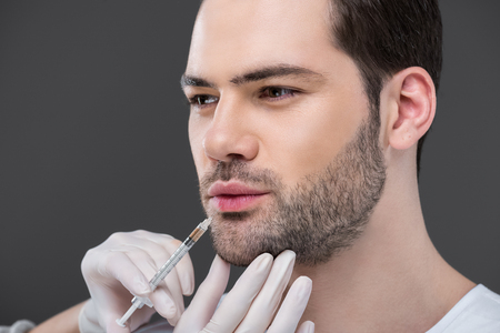 hands in medical gloves making beauty injection for bearded man, isolated on grey Foto de archivo - 114409312