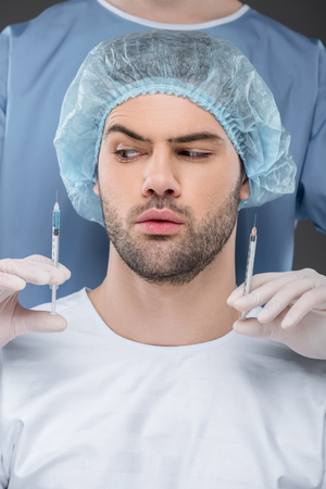 bearded handsome man in medical cap choosing beauty injections, isolated on grey