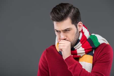 sick man coughing in warm scarf, isolated on grey Stock Photo