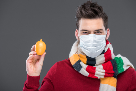 sick man in warm scarf and medical mask holding lemon, isolated on grey