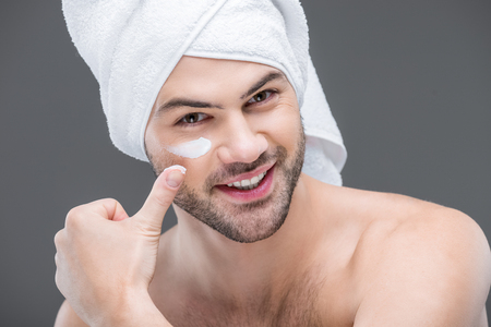 cheerful beardman in towel applying face cream, isolated on grey, skin care concept
