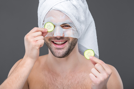 cheerful bearded man with collagen mask and cucumber slices, isolated on grey, skin care concept
