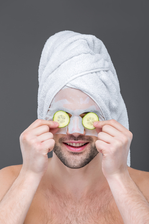 man with towel, collagen mask and cucumber slices on eyes, isolated on grey, skin care concept Reklamní fotografie
