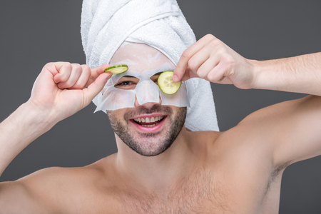 smiling man with collagen mask and cucumber slices, isolated on grey, skin care concept